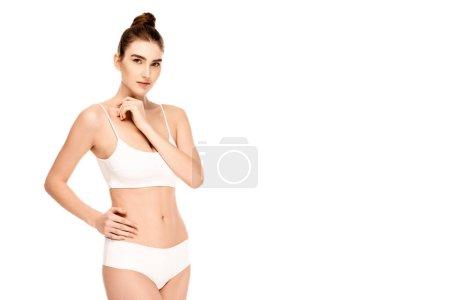 jeune modèle en haut et culotte debout avec la main sur la hanche et en regardant la caméra isolée sur blanc