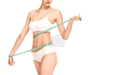 Photo pour Vue recadrée de la taille de la femme mesurant avec ruban à mesurer isolé sur blanc - image libre de droit