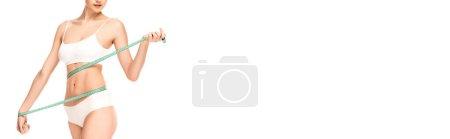 Photo pour Recadrage panoramique de femme mesurant la taille avec ruban à mesurer isolé sur blanc - image libre de droit