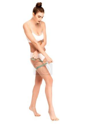 Photo pour Femme pieds nus en haut et culotte mesurant cuisse isolé sur blanc - image libre de droit