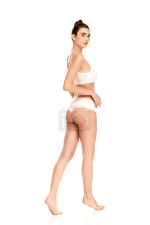 Photo for Young barefoot woman with perfect body looking at camera and standing on white - Royalty Free Image