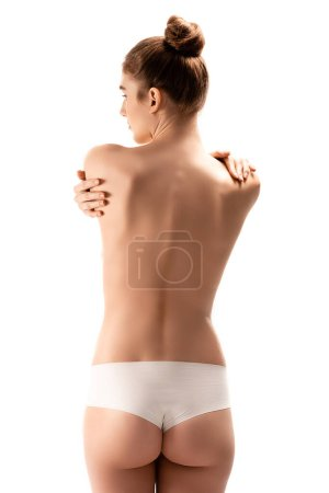Photo pour Vue arrière de la femme en culotte debout et se câlinant isolée sur blanc - image libre de droit