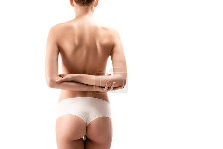 Photo pour Vue arrière de la jeune femme en culotte debout avec les bras croisés derrière le dos isolé sur blanc - image libre de droit