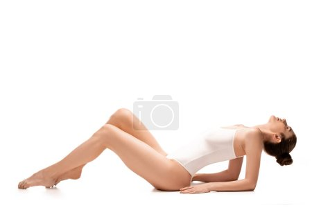 Photo for Side view of barefoot woman in bodysuit lying on white - Royalty Free Image