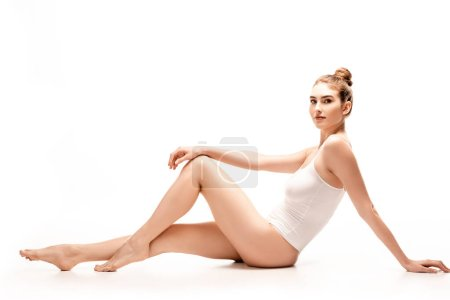 Photo for Barefoot and slim young woman in bodysuit sitting on white - Royalty Free Image