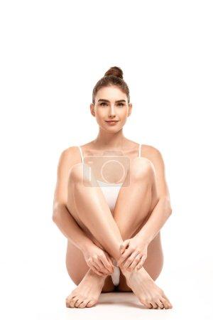Photo pour Jeune femme en body assis avec les jambes croisées sur blanc - image libre de droit