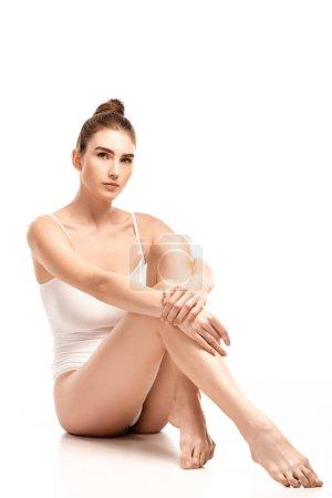 pieds nus jeune femme en body assis tout en regardant la caméra sur blanc