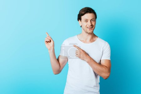 Man in white t-shirt pointing with fingers on blue background