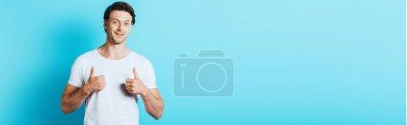Photo pour Image horizontale de l'homme en t-shirt blanc montrant les pouces sur fond bleu - image libre de droit