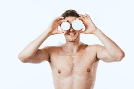 Hemdloser Mann hält Gläser mit kosmetischen Cremes isoliert auf weiß