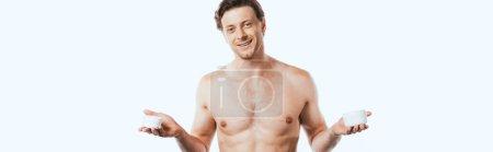 Panoramaorientierung des hemdlosen Mannes, der Gläser mit kosmetischen Cremes auf weiß isoliert hält