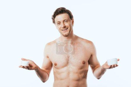 Muskulöser Mann hält Gläser mit kosmetischen Cremes auf weiß isoliert