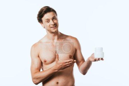 Hemdloser Mann zeigt mit der Hand auf Gläser mit Kosmetikcremes