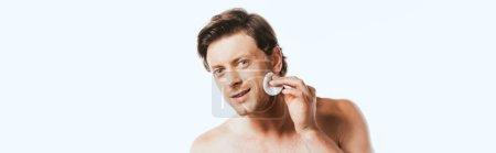 Photo pour Prise de vue panoramique d'un homme torse nu tenant un coton près du visage isolé sur du blanc - image libre de droit