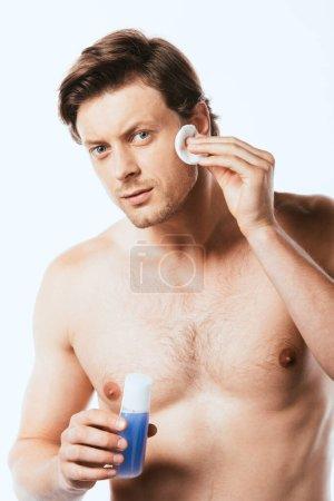 Photo pour Homme sans chemise appliquant toner avec coton sur le visage isolé sur blanc - image libre de droit