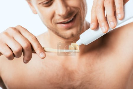 Photo for Cropped view of shirtless man holding toothbrush and toothpaste isolated on white - Royalty Free Image