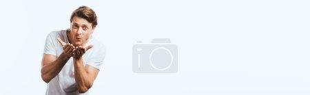 Horizontales Konzept junger Mann pustet Luftkuss in Kamera isoliert auf Weiß