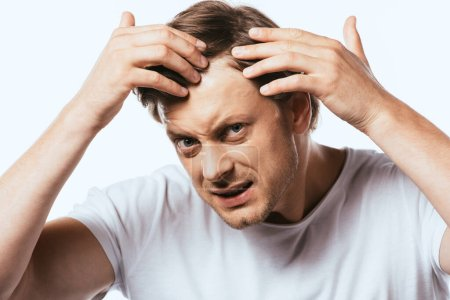 Dissatisfied man touching hair and looking at camera isolated on white
