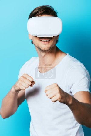 Photo for Young man in virtual reality headset showing fists on blue background - Royalty Free Image