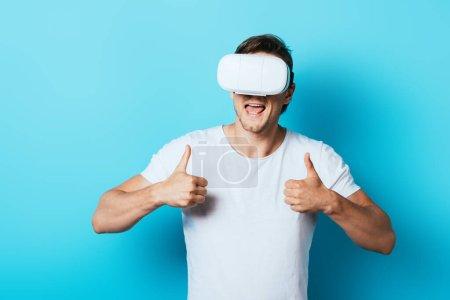 Jeune homme montrant pouces levés tout en utilisant un casque de réalité virtuelle sur fond bleu
