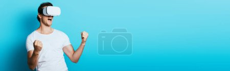 Photo for Panoramic image of man in vr headset showing yes gesture on blue background - Royalty Free Image