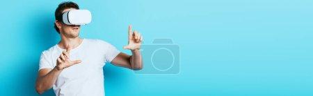 Photo pour Récolte horizontale de l'homme en vr casque pointant avec les doigts sur fond bleu - image libre de droit