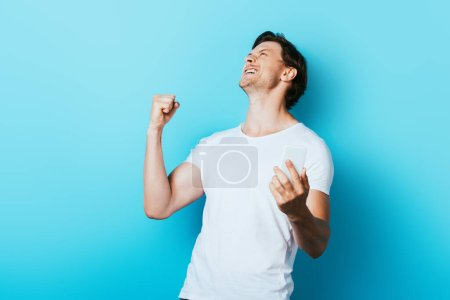 Young man showing yes gesture while holding smartphone on blue background