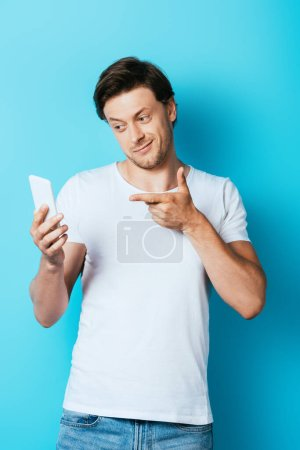 Man in white t-shirt pointing with finger at smartphone on blue background