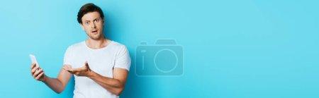 Photo pour Vue panoramique de l'homme confus regardant la caméra tout en pointant vers le smartphone sur fond bleu - image libre de droit