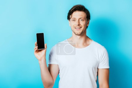 Young man looking at camera while showing smartphone with blank screen on blue background