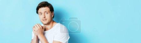 Photo pour Image horizontale de l'homme effrayé regardant loin sur fond bleu - image libre de droit