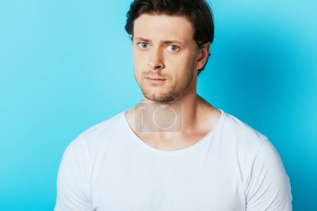 Photo for Serious man in white t-shirt looking at camera on blue background - Royalty Free Image