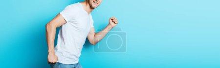 Cultivo panorámico del hombre en camiseta blanca sobre fondo azul