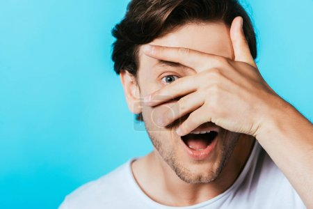 Excited man with hand near face looking at camera isolated on blue