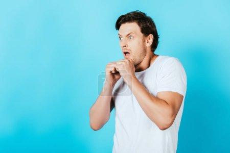 Photo pour Homme fou en t-shirt blanc avec les mains dans les poings regardant loin sur fond bleu - image libre de droit