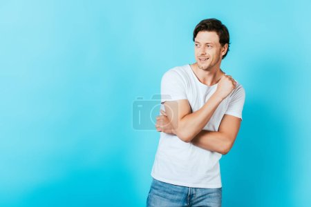 Young man in white t-shirt looking away on blue background