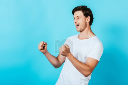 Young man in white t-shirt showing yeah gesture on blue background