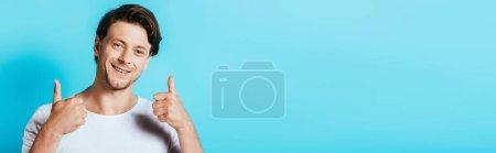 Photo pour Récolte panoramique de l'homme montrant pouces vers le haut à la caméra sur fond bleu - image libre de droit