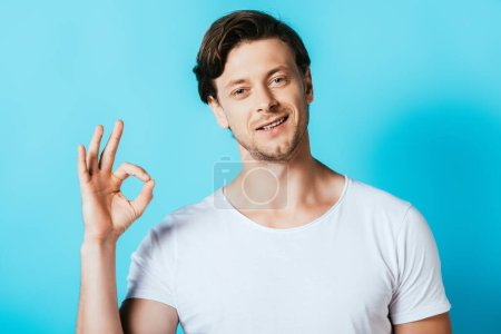 Man in white t-shirt showing okay gesture on blue background