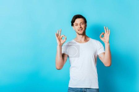 Junger Mann im weißen T-Shirt zeigt Okay-Geste vor Kamera auf blauem Hintergrund