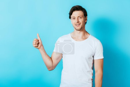 Photo for Young man in white t-shirt showing thumb up on blue background - Royalty Free Image