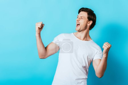 Young man in white t-shirt showing yes gesture on blue background