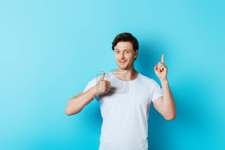 Photo for Young man in white t-shirt showing thumb up and having idea on blue background - Royalty Free Image