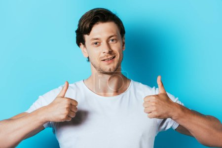 Man in white t-shirt showing thumbs up on blue background