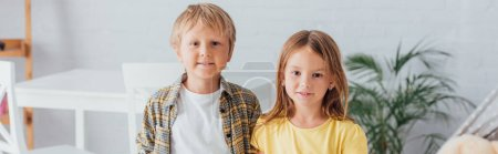 Photo for Panoramic shot of brother and sister looking at camera while standing at home - Royalty Free Image