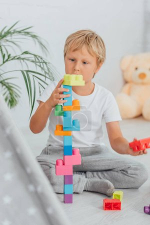Photo for Selective focus of boy in pajamas sitting on floor and playing with multicolored building blocks - Royalty Free Image