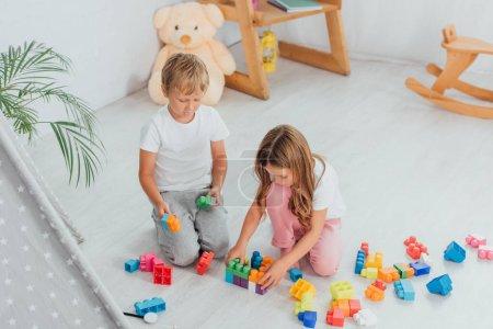 Photo pour Vue grand angle des enfants jouant avec des blocs de construction assis sur le sol en pyjama - image libre de droit