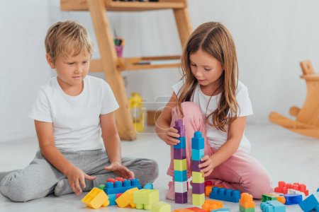 concentrated kids in pajamas playing with building blocks while sitting on floor