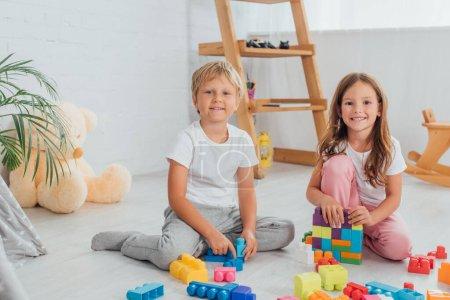 Photo pour Excité frère et sœur en pyjama assis sur le sol près des blocs de construction et regardant la caméra - image libre de droit