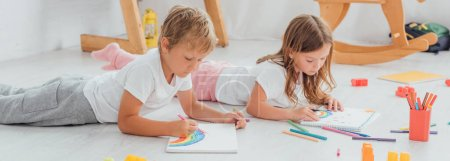 Photo for Concentrated brother and sister in pajamas lying on floor and drawing with felt pens in sketchbooks - Royalty Free Image